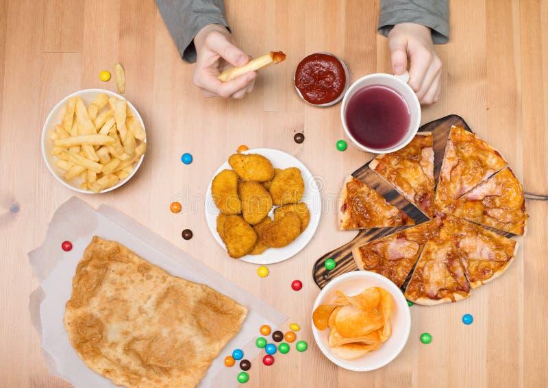 Lura att äta pizza, klumpar, chiper och annan snabbmat Skjutit i en studio royaltyfri fotografi