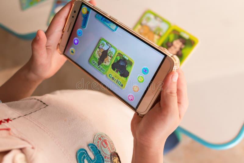 Lura att spela ökad verklighet som är popup av triceratops och gorilla via mobil arkivbild