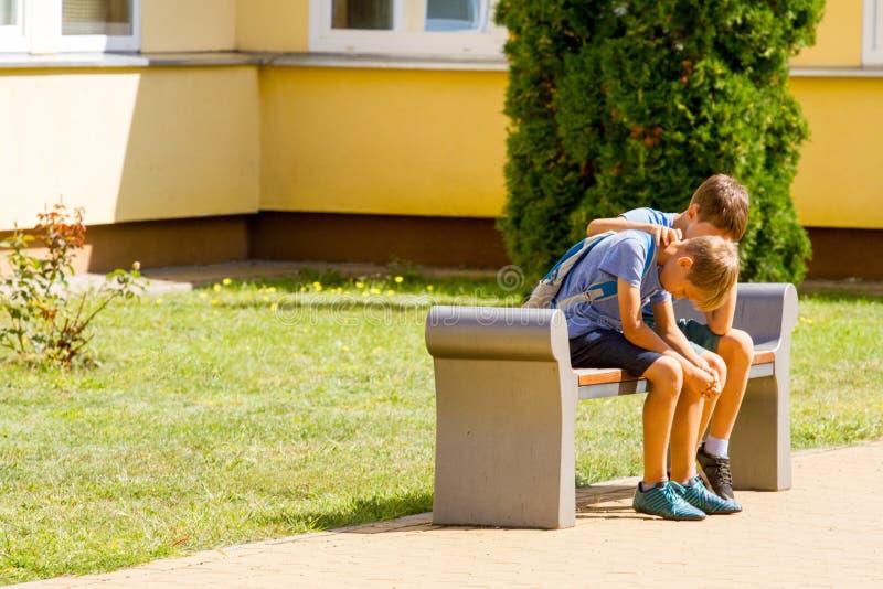 Lura att trösta trösta den upprivna ledsna pojken i skolgård arkivfoton