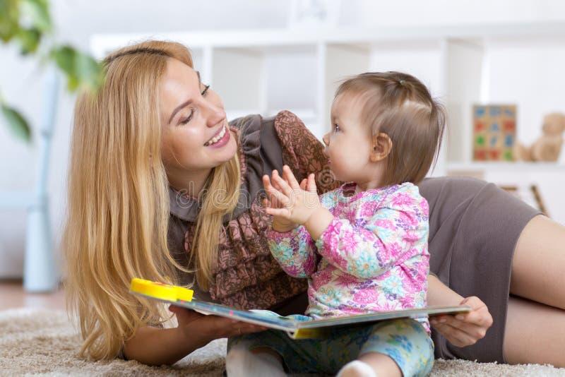 Lura flickan, och modern läste en bok inomhus royaltyfri bild