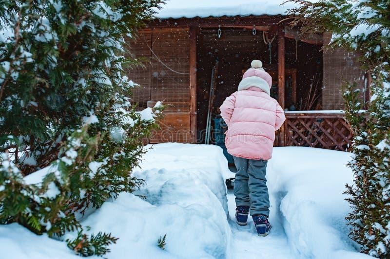 Lura flickan som hjälper att göra ren bana från snö med skyffeln arkivfoto