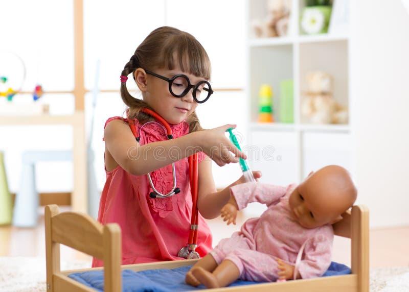 Lura flickan som spelar en doktor med dockan i dagis royaltyfri fotografi
