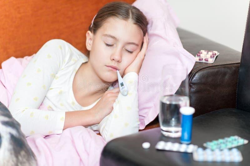 Lura låsförkylning som ligger i säng med termometern som mäter temperatu royaltyfria foton