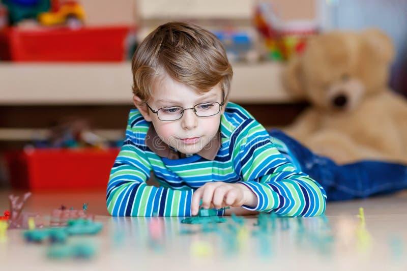 Lura pojken som inomhus spelar med leksaksoldater på barnkammaren arkivfoto