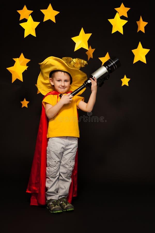 Lura pojken som spelar himmeliakttagaren med ett teleskop arkivfoto