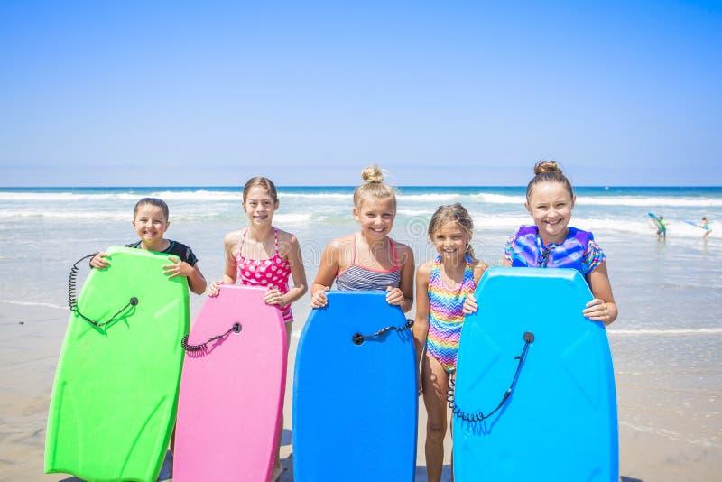 Lurar att spela på stranden tillsammans medan på semester royaltyfria bilder
