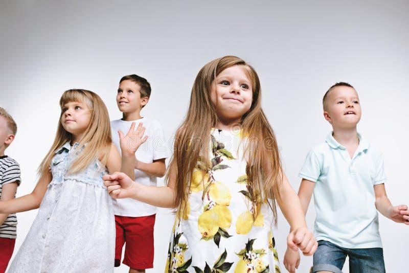 Lurar det gulliga förskolebarnet för gruppmode vänner som tillsammans poserar och ser vit bakgrund för kameran fotografering för bildbyråer