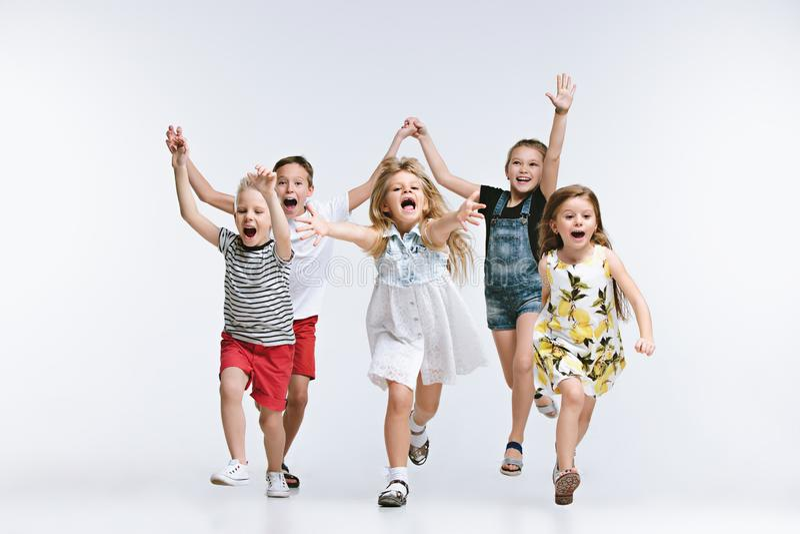 Lurar det gulliga förskolebarnet för gruppmode vänner som tillsammans poserar och ser vit bakgrund för kameran royaltyfri fotografi