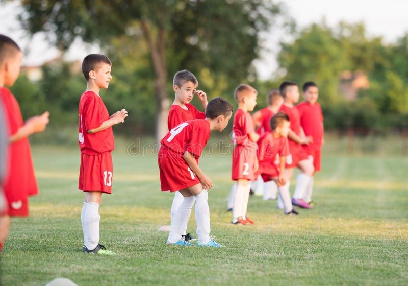 Lurar fotbollfotboll - barnspelare som övar för match royaltyfri bild