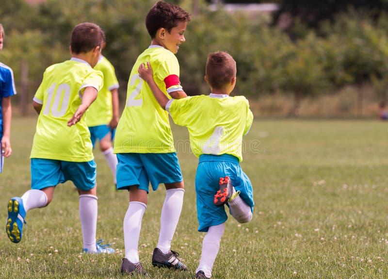 Lurar fotbollfotboll - barnspelare som firar efter victo arkivfoton