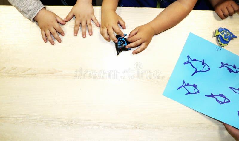 Lurar gruppdanandekonsthantverk i dagis Barn som spenderar tid i daghem med det stora intresset arkivbild