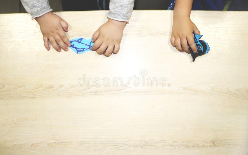 Lurar gruppdanandekonsthantverk i dagis Barn som spenderar tid i daghem med det stora intresset royaltyfria foton