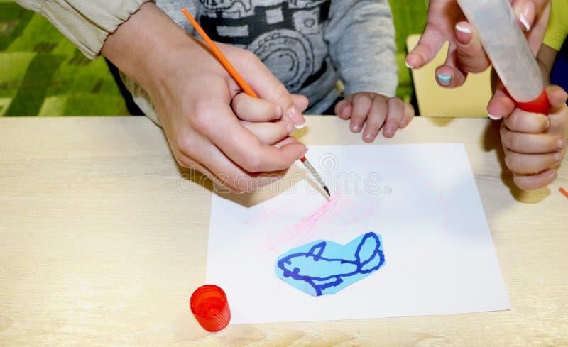 Lurar gruppdanandekonsthantverk i dagis Barn som spenderar tid i daghem med det stora intresset royaltyfri fotografi