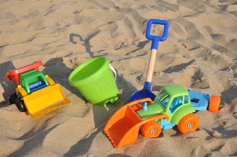 Lurar leksaker på den sandiga stranden royaltyfri bild