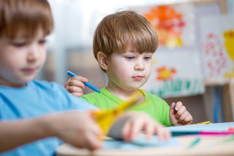 Lurar pojkar som hemma målar i barnkammare arkivbild