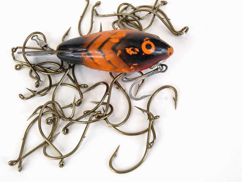 Lure and Hooks. An orange fish shaped lure and fishing hooks over a white background royalty free stock photo