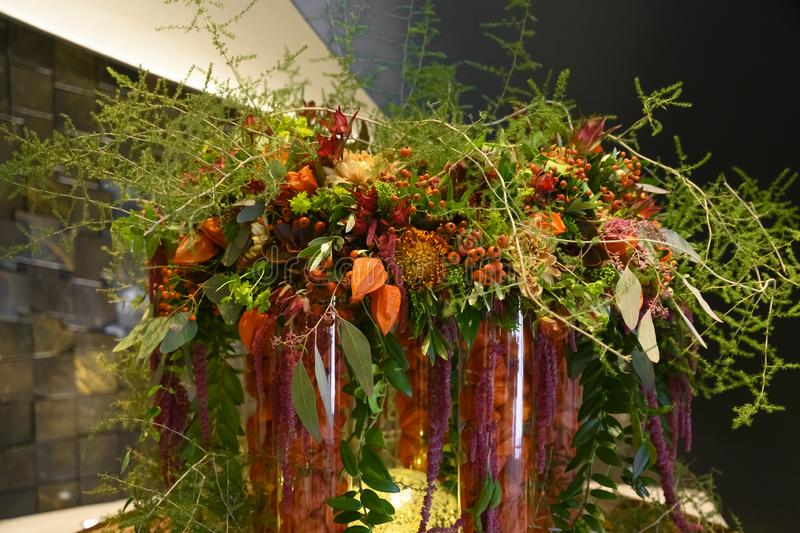 Lush autumn flower arrangement with physalis, asters, berries, leaves and ferny asparagus. Vases filled with physalis decorated with orange, yellow and red stock images