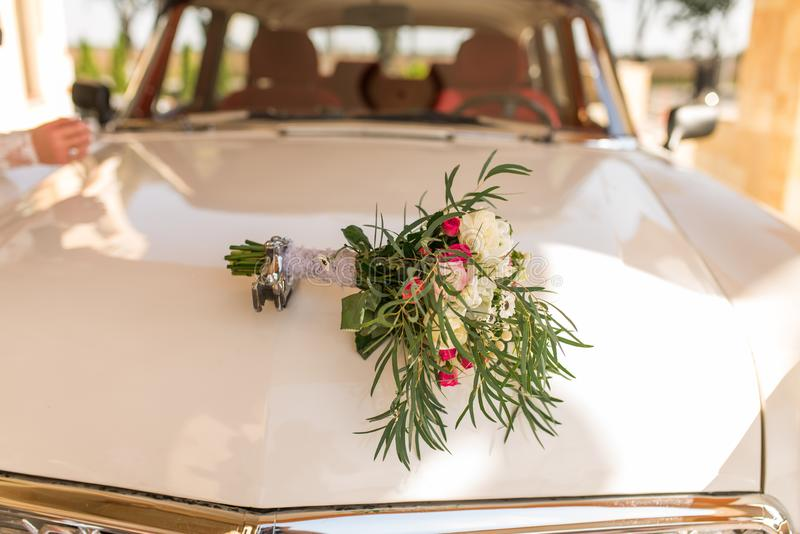 Lush bridal bouquet with white and pink flowers with a lot of greenery lying on the hood of white car of bride and groom. Wedding royalty free stock photo