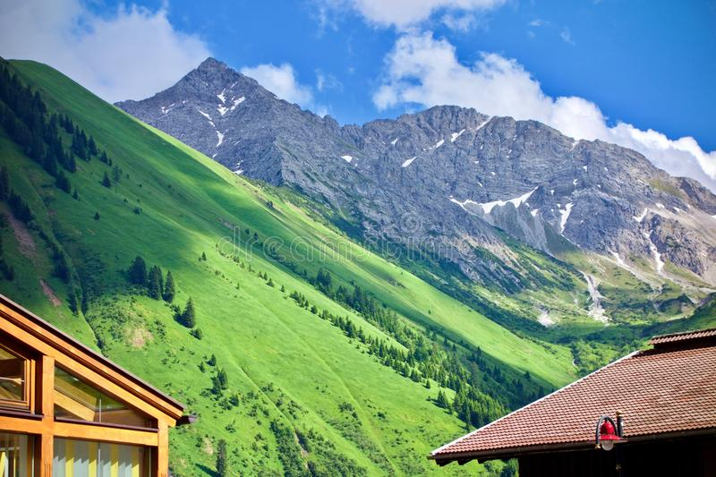 Lush green alpine peaks and valley. Peaceful scenic landscape of lush green alpine peaks and valley under a blue cloudy sky with the roofs of two chalets in the stock photo