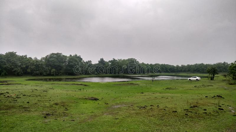 Lush green jungle, lake and grass with overcast monsoon sky and a white car. A natural landscape with overcast cloudy sky, a lake, green foliage and hills stock images