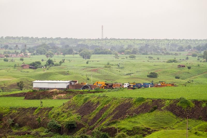 Lush Green Meadows and overcast monsoon sky near a mining site. Lush Green Meadows and overcast grey monsoon sky in Indian country side or village stock images
