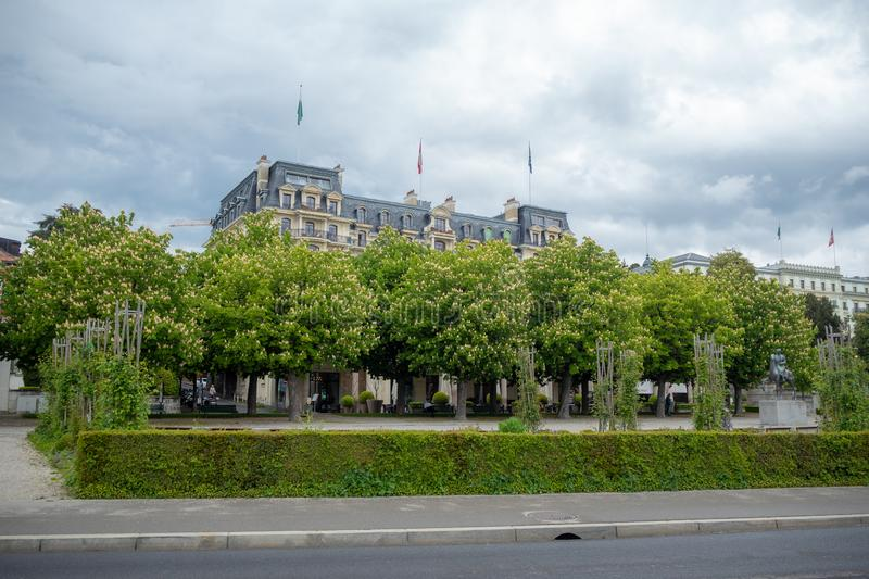 Lush green trees in the garden in front of the medieval style hotel on cloudy sky background. Lausanne, Switzerland stock image