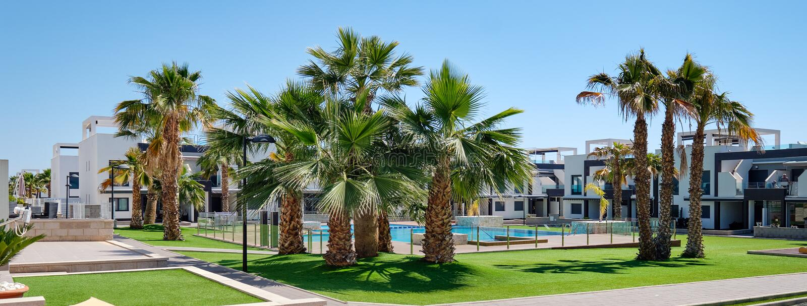 Lush palm trees inside of closed urbanization with green lawn swimming pool modern houses at sunny summer day. New property in Spain, no people, horizontal royalty free stock image