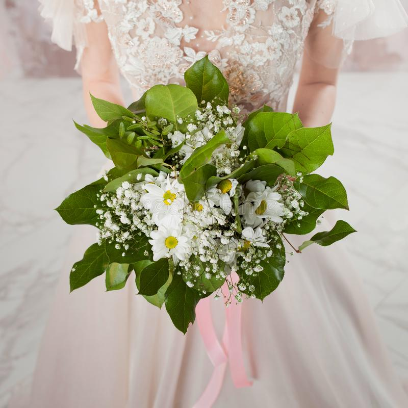 Lush wedding bouquet in the hands of the bride. A girl in a wedding dress holding a bouquet stock image
