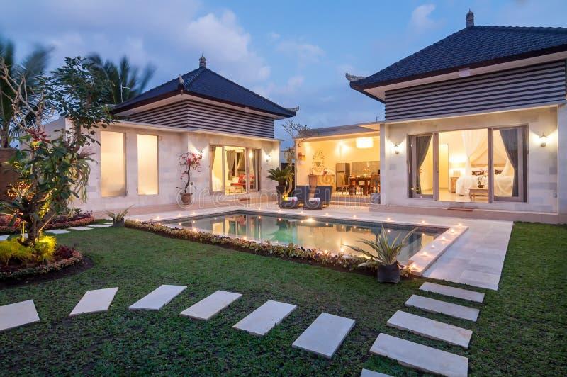 Lusso del tiro di notte e villa privata con lo stagno all'aperto fotografie stock libere da diritti