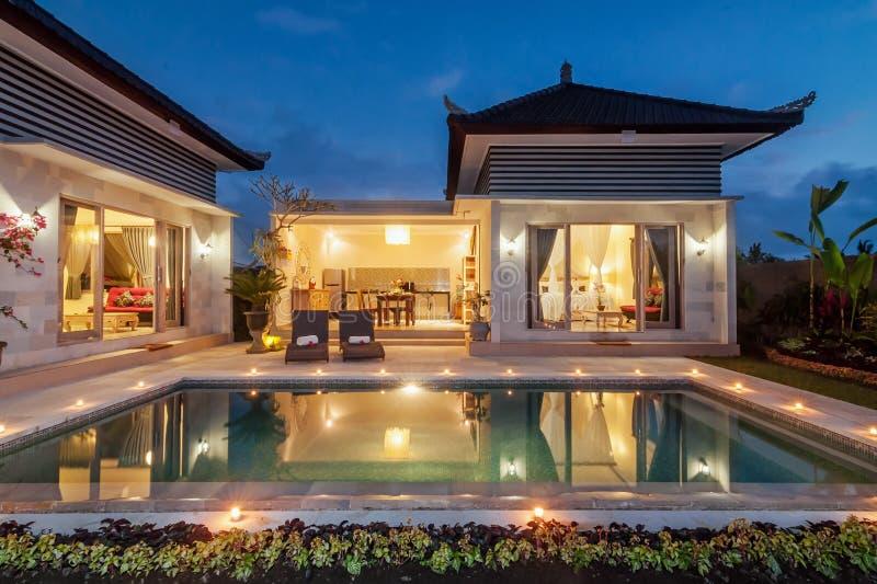 Lusso del tiro di notte e villa privata con lo stagno all'aperto fotografia stock
