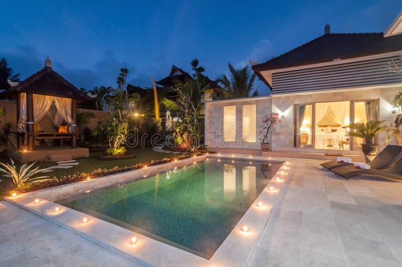Lusso del tiro di notte e villa privata con lo stagno all'aperto immagini stock