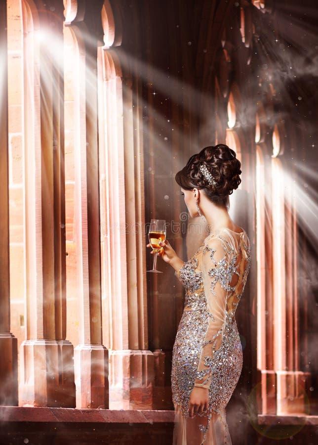 Lusso. Giovane donna in vestito da sera con vetro di Champagne Standing alla finestra in sole immagine stock libera da diritti