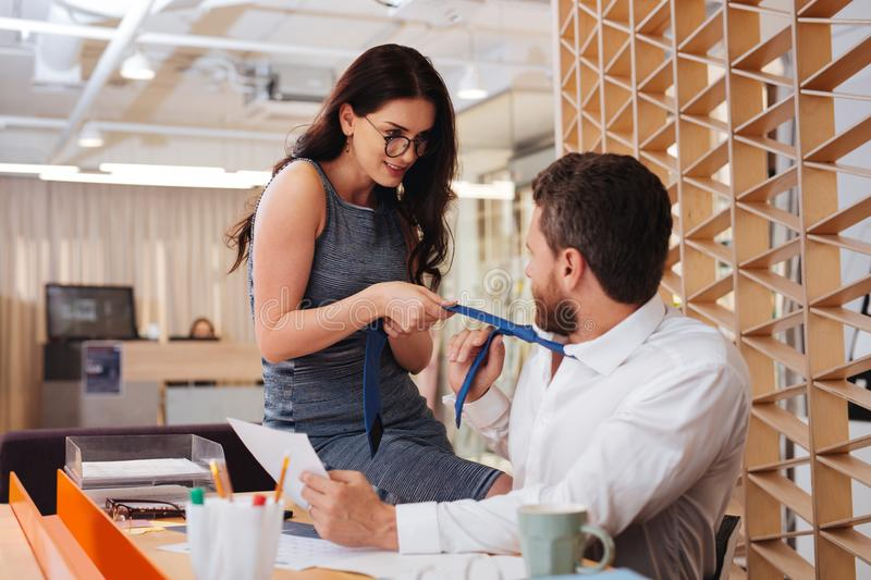 Lustful woman holding her boss tie. Come to me. Passionate pretty women seducing her boss while sitting on his table royalty free stock photos