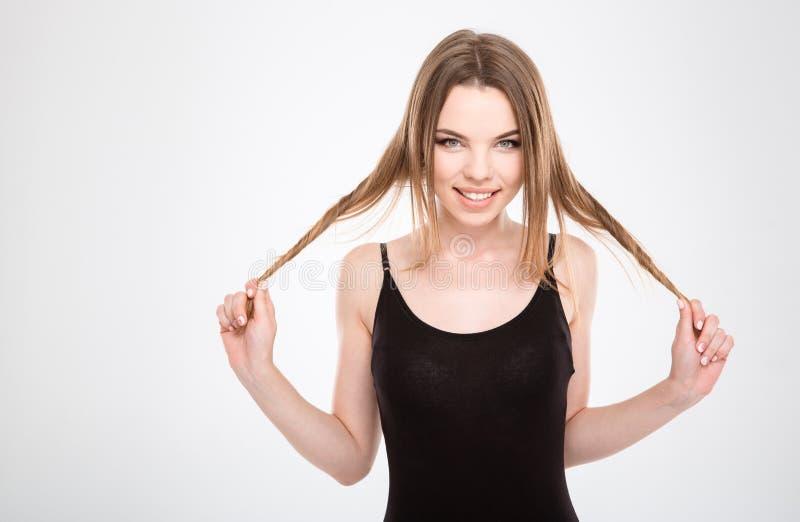 Lustig, die recht junge Frau unterhalten, die mit dem Haar spielt lizenzfreies stockfoto