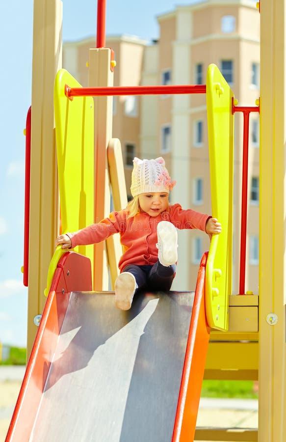Lustig wenig Mädchen auf Spielplatz Kind auf Dia lizenzfreies stockbild