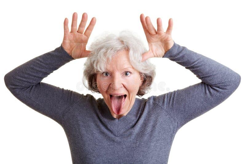 Lustige ältere Frau, die sie zeigt lizenzfreies stockfoto