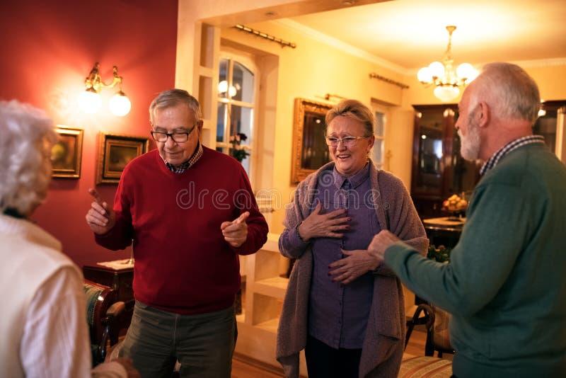 Lustige ältere Leute, die zu Hause Partei lächeln und tanzen lizenzfreies stockfoto