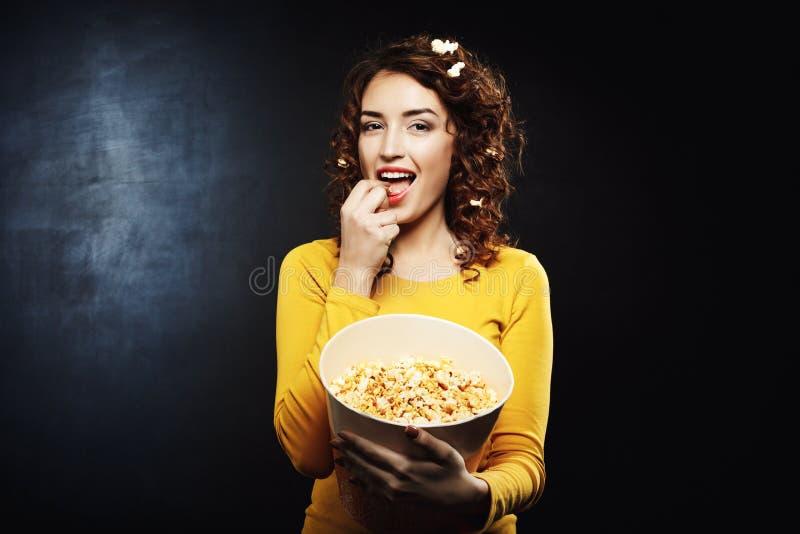 Lustige attraktive Frau, die geschmackvolles salziges süßes Popcorn am Kino isst lizenzfreie stockfotos