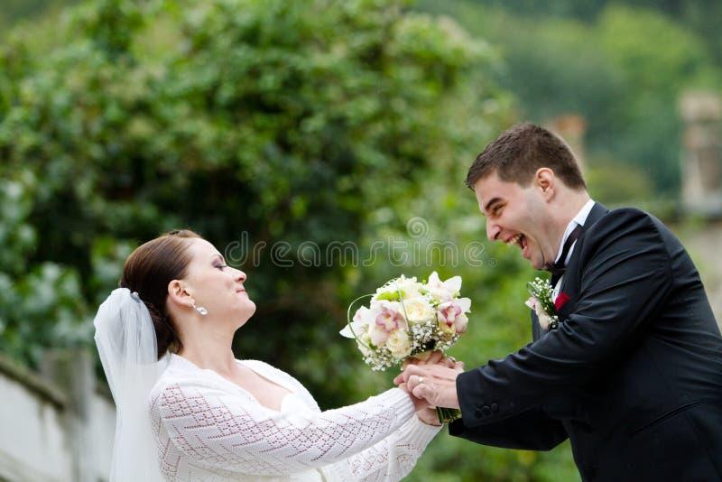 Lustige Braut und Bräutigam mit Hochzeits-Blumenstrauß lizenzfreie stockfotos
