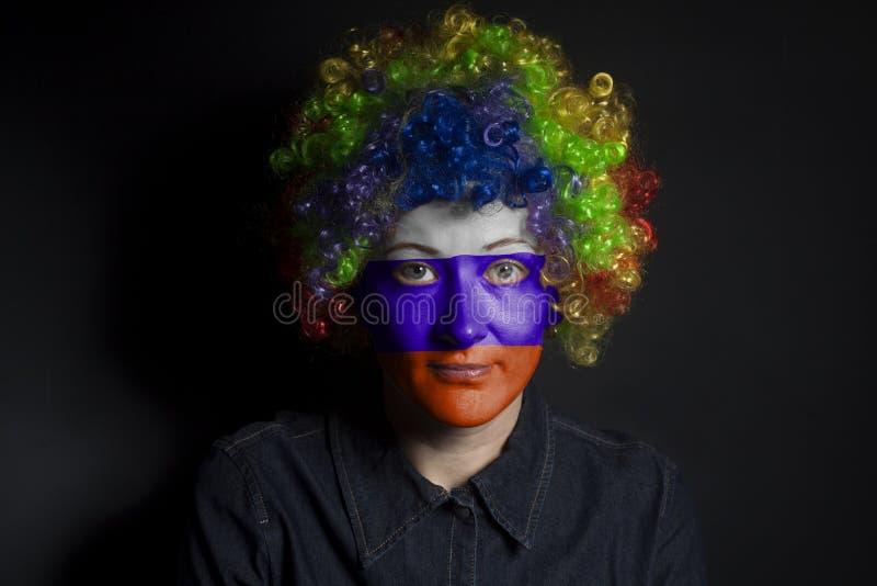 Lustige Clownfrau mit gemalter russischer Flagge stockbild