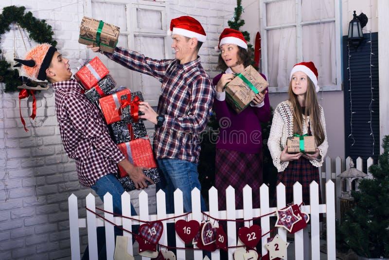 Lustige Familie mit Geschenken in ihren Händen geht am Weihnachten stockfotografie