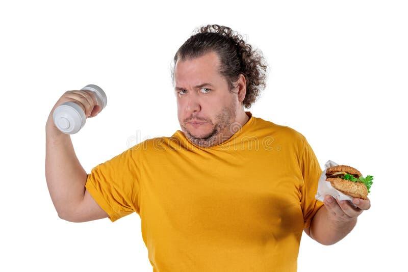 Lustige fette Fleisch fressende ungesunde Nahrung und Versuchen, die Übung zu nehmen lokalisiert auf weißem Hintergrund stockfotos