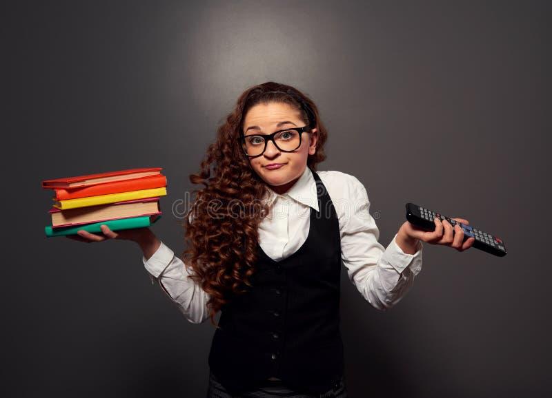Lustige Frau in den Gläsern mit Stapel der Bücher und der Fernsehentfernten station stockbild