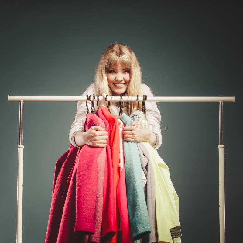 Lustige Frau, die alle Kleidung im Mall oder in der Garderobe nimmt stockfoto