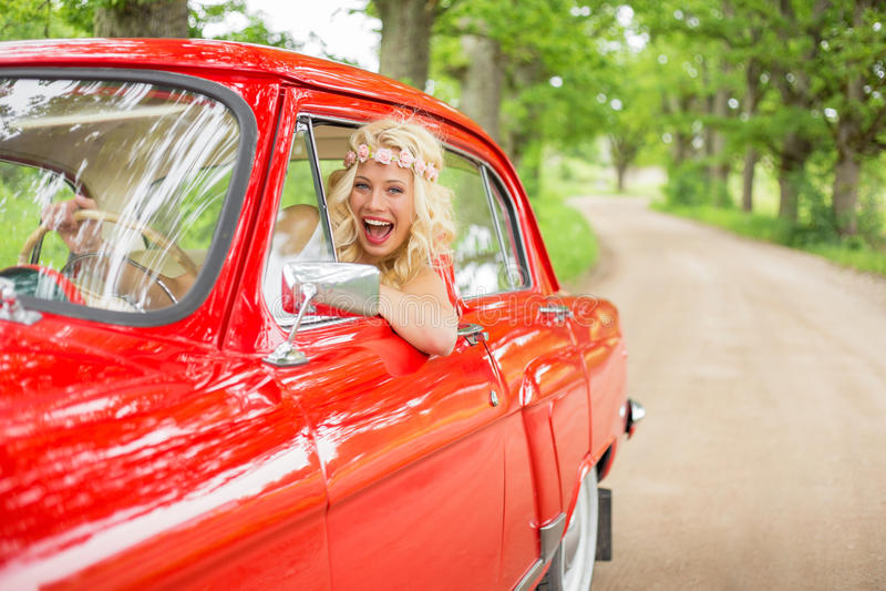 Lustige Frau, die den Spaß fährt rotes Weinleseauto hat stockbilder