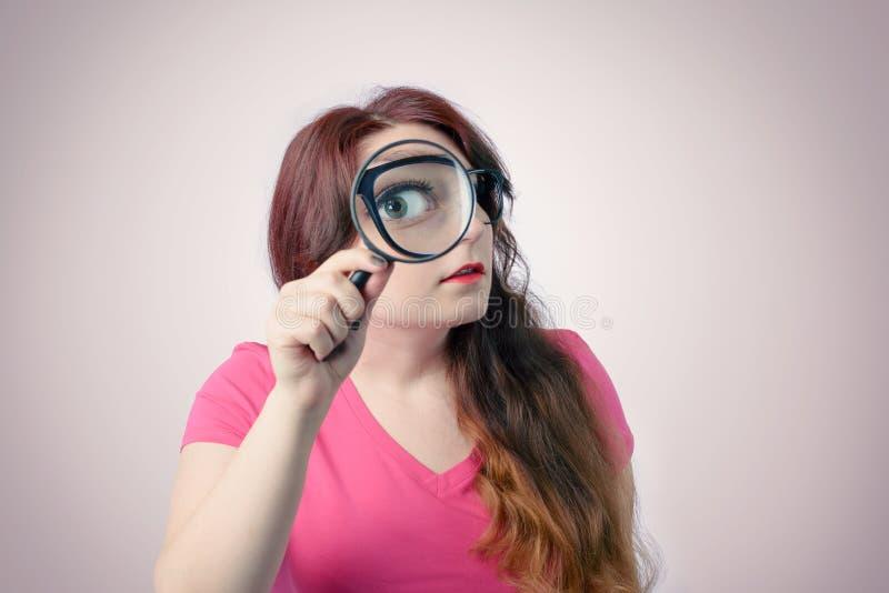 Lustige Frau, die Lupe verwendet Großes Zoomkonzept lizenzfreies stockfoto
