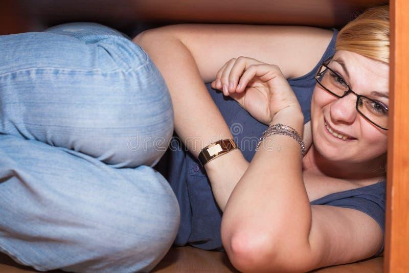 Lustige Frau, die unter Tabelle sich versteckt stockfotos