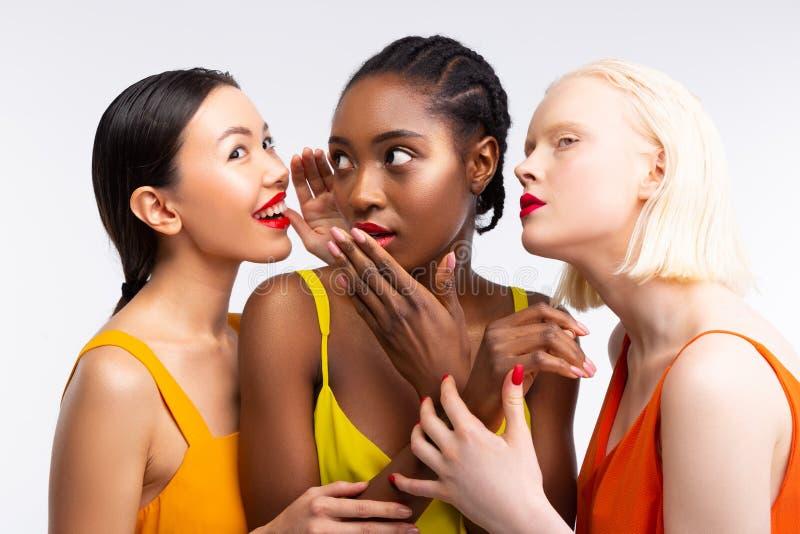 Lustige Frauen mit unterschiedlicher Haut klatschend ?ber ihre Leben stockfotos