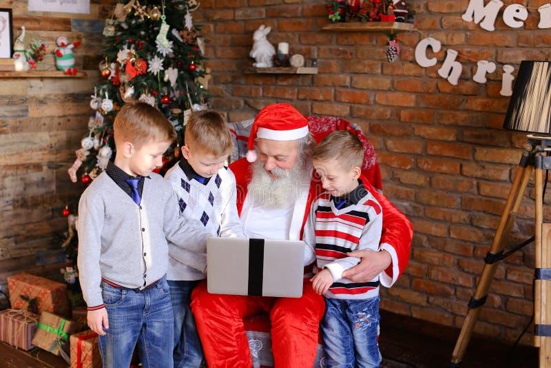Lustige Freunde verhindern Santa Claus an Einrichtungsgeschenken auf L stockfotografie