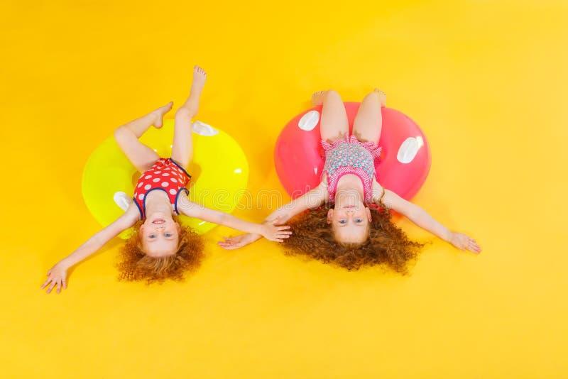 Lustige glückliche Kinder mit schwimmendem Kreis auf einem farbigen Hintergrund Seashells gestalten auf Sandhintergrund Babyspaß  lizenzfreie stockfotos